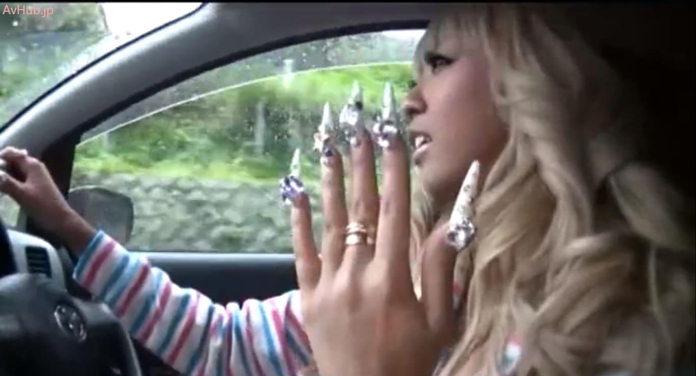泉麻那がスーパーロングデコネイルの手でハンドルを持つ車